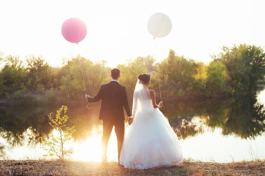 Mariés tenant des ballons devant un étang