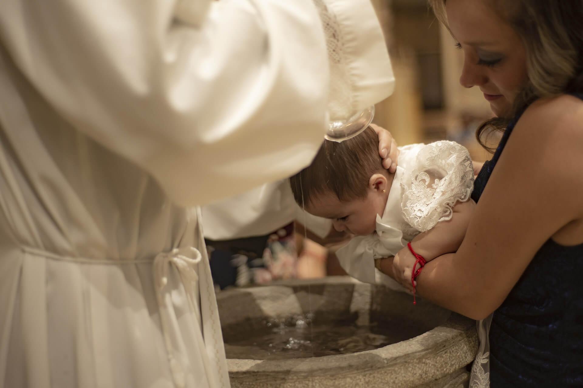Marraine qui tient le baptisé dans ses bras lors d'un baptême